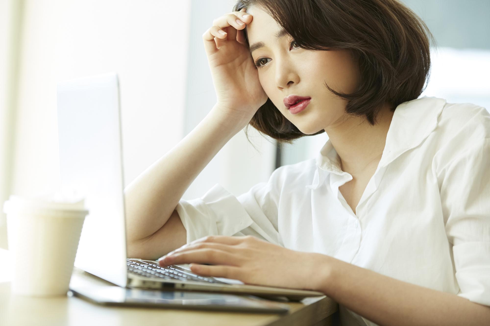 パソコンの画面を見ながら憂鬱そうな女性